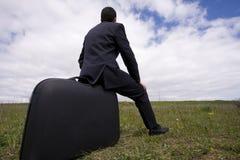 O homem de negócios senta-se em sua bagagem Imagem de Stock