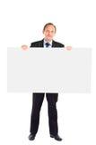 o homem de negócios sustenta uma folha branca vazia Fotografia de Stock Royalty Free