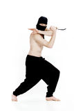 O homem de Ninja guarda a faca e está pronto para atacar no fundo branco Fotos de Stock