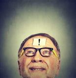 O homem de pensamento idoso com vidros e a exclamação assinam a marca na testa que olha acima Foto de Stock Royalty Free