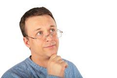 O homem de pensamento nos vidros olha acima Fotos de Stock Royalty Free