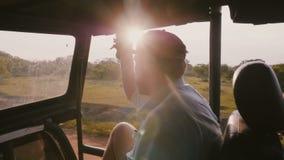 O homem de relaxamento feliz novo do viajante no passeio tropical no carro do safari, luz solar da excursão da floresta do por do vídeos de arquivo