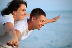 O homem de sorriso e a mulher nova coloc as mãos nos lados Imagens de Stock Royalty Free