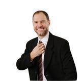 O homem de sorriso em um terno endireita seu laço Imagem de Stock Royalty Free
