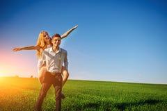 O homem de sorriso está guardando sobre sua mulher feliz traseira, que retira seus braços e simula um voo na perspectiva do s azu imagens de stock royalty free