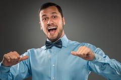 O homem de sorriso está gesticulando com a mão, apontando o dedo mostra-se Imagens de Stock Royalty Free