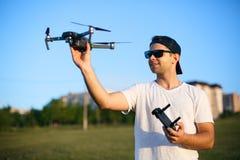O homem de sorriso feliz guarda o zangão compacto pequeno e o controlador remoto em suas mãos O piloto lança o quadcopter de sua  imagem de stock