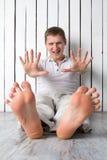 O homem de sorriso mostra os dedos que sentam-se perto da parede Fotos de Stock