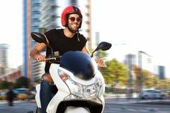O homem de sorriso na motocicleta monta na rua da cidade imagens de stock royalty free