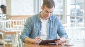 O homem de sorriso novo é ocupado com sua tabuleta digital vídeos de arquivo