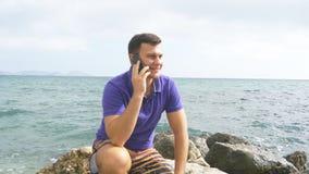 O homem de sorriso novo está falando no telefone celular na praia no mar Indivíduo feliz considerável que senta-se na pedra perto imagem de stock