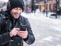 O homem de sorriso que anda na cidade no inverno e que escuta a música através dos fones de ouvido conectou aos bu do telefone do Fotos de Stock