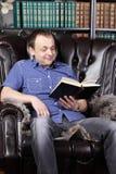 O homem de sorriso senta-se na poltrona de couro e lê-se o livro Imagens de Stock Royalty Free