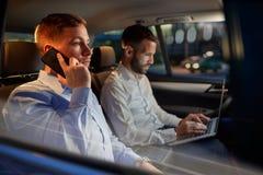 O homem de trabalho do noite-negócio usa o smartphone no carro Fotos de Stock Royalty Free