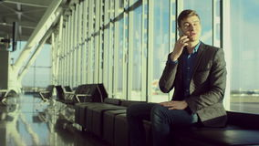 O homem de vista agradável novo está falando sobre um telefone celular no aeroporto vídeos de arquivo