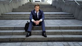 O homem decepcionado no terno que senta-se nas escadas, más entrelaça, oportunidades perdidas imagens de stock