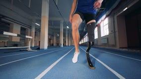 O homem deficiente com um pé protético está aquecendo-se antes do corredor vídeos de arquivo