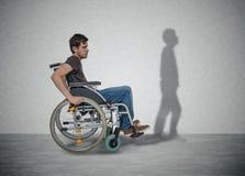 O homem deficiente dos jovens na cadeira de rodas tem a esperança para a recuperação Sua sombra está andando próximo fotos de stock