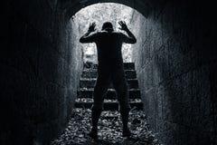 O homem deixa o túnel de pedra escuro com as mãos levantadas Fotografia de Stock Royalty Free