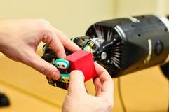 O homem deixa o robô mecânico entregar guardar um cubo vermelho no laboratório de pesquisa imagens de stock