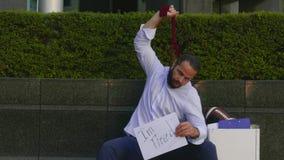 O homem demitido está sentando-se na rua e está estrangulando-se com uma exibição do laço que agora seja duro viver, a vídeos de arquivo