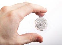 O homem demonstra o russo novo 25 rublos de moeda Fotografia de Stock