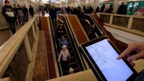 O homem dentro examina no subsolo o mapa do metro usando a tabuleta filme
