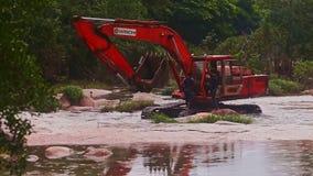 O homem derrama a água da cubeta na máquina escavadora Cab contra plantas filme