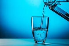 O homem derrama a água do vidro imagem de stock