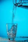 O homem derrama a água do vidro fotos de stock