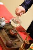 O homem derrama a água no teapot na bandeja de chá Foto de Stock