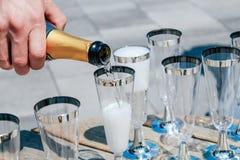 O homem derrama o champanhe em vidros Close-up imagens de stock royalty free