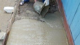 O homem derrama o cimento de uma cubeta video estoque