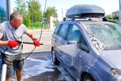 O homem derrama o corpo de carro ativo da espuma M?quina limpa de Washington do carro, lavagem de carro com esponja e mangueira C fotografia de stock royalty free