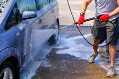 O homem derrama o corpo de carro ativo da espuma M?quina limpa de Washington do carro, lavagem de carro com esponja e mangueira C imagem de stock