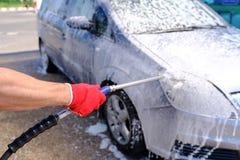 O homem derrama o corpo de carro ativo da espuma M?quina limpa de Washington do carro, lavagem de carro com esponja e mangueira C foto de stock