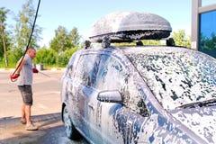 O homem derrama o corpo de carro ativo da espuma M?quina limpa de Washington do carro, lavagem de carro com esponja e mangueira C imagem de stock royalty free