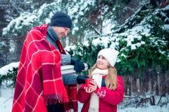 O homem derrama o chá quente fora da garrafa térmica para sua filha foto de stock