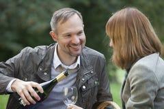 O homem derrama o champanhe em um vidro Imagens de Stock Royalty Free