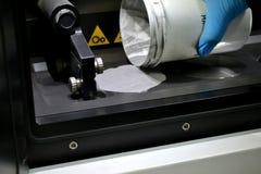O homem derrama o pó de metal na câmara de uma máquina da aglomeração do laser imagens de stock