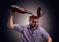 O homem derrama sua cabeça sobre com álcool fotos de stock