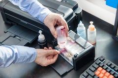 O homem derrama a tinta vermelha na impressora da foto fotografia de stock royalty free