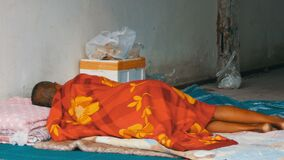 O homem desabrigado dorme no véu vermelho na rua da cidade O problema da pobreza no mundo video estoque