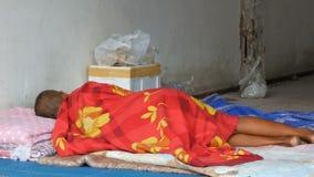O homem desabrigado dorme no véu vermelho na rua da cidade O problema da pobreza no mundo filme