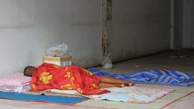 O homem desabrigado dorme no véu vermelho na rua da cidade O problema da pobreza no mundo vídeos de arquivo