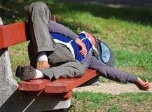 O homem desabrigado está dormindo em um banco de parque Foto de Stock