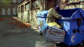 O homem desabrigado que procuram por garrafas vazias e o outro material por reciclam video estoque