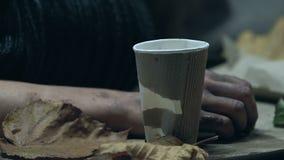 O homem desabrigado que treme na rua fria, implorando o dinheiro, moeda cai no copo de papel video estoque