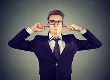O homem desagradado que obstrui as orelhas com ` t do doesn dos dedos quer escutar foto de stock