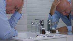O homem desapontado no sofrimento da sala do toalete e o doente de sentimento pensam para tomar comprimidos fotos de stock royalty free